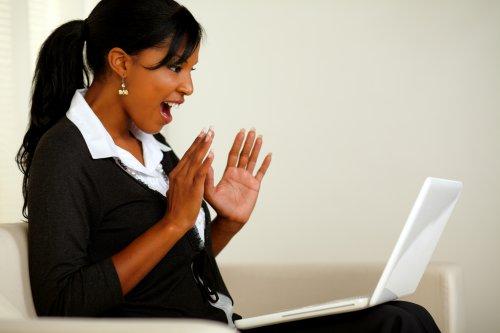 Ảnh chụp chân dung của một phụ nữ trẻ ngạc nhiên khi đọc một tin tức kinh doanh tuyệt vời trên máy tính xách tay