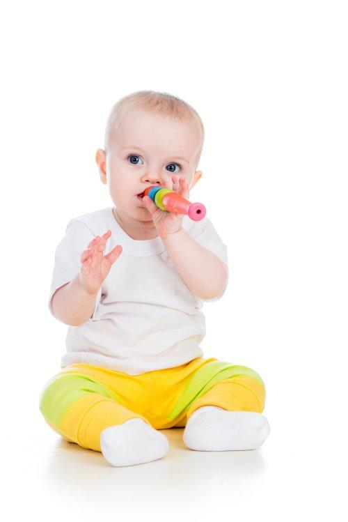 Ảnh chụp bé gái chơi với đồ chơi âm nhạc bị cô lập trên nền trắng