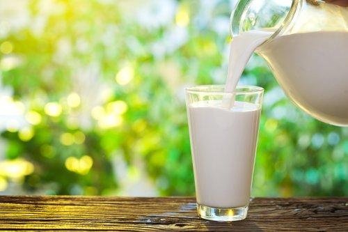 Ảnh chụp  Đổ sữa vào ly trên nền thiên nhiên