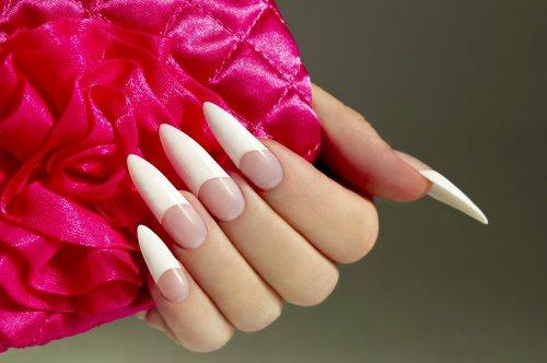 Ảnh chụp móng tay trắng của một phụ nữ với phụ kiện hoa hồng trên nền tối