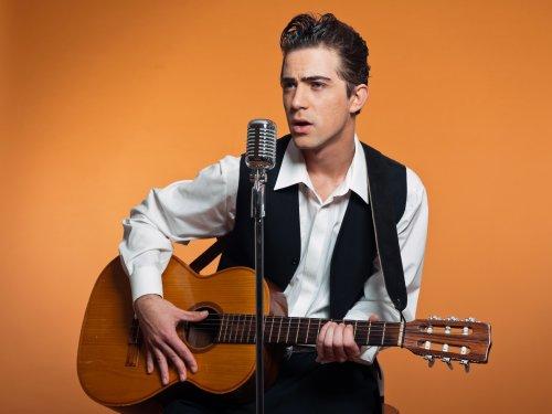 Ảnh chụp ca sĩ nhạc đồng quê mặc bộ vest đen với cây đàn guitar