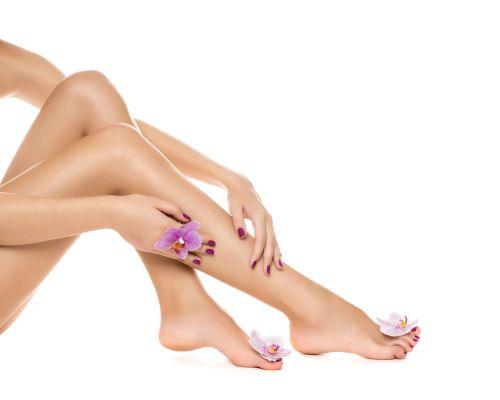 Ảnh chân dung của người phụ nữ chăm sóc da chân và hoa lan trên nền trắng