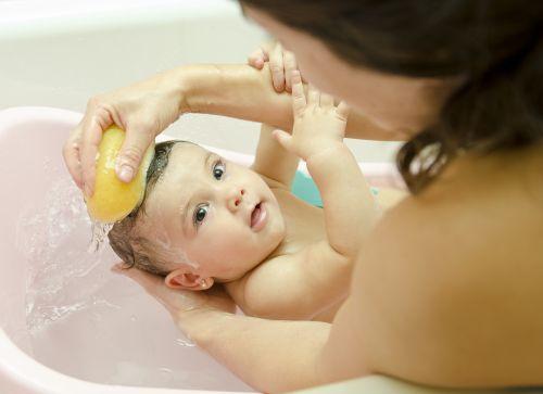 Ảnh chụp mẹ vệ sinh cho bé trong bồn tắm với bọt biển