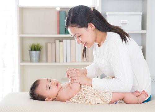 Hình ảnh Mẹ châu Á xoa bóp tay bé ở nhà.