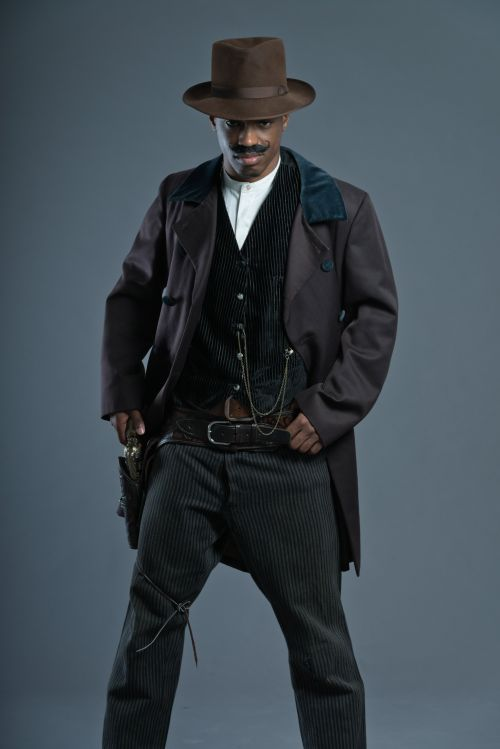 Ảnh chụp người đàn ông cao bồi tây phương với ria mép mang khẩu súng và mũ nâu