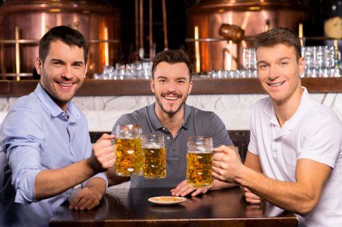 Ảnh chụp Ba người bạn vui vẻ cầm ly bia và mỉm cười với camera