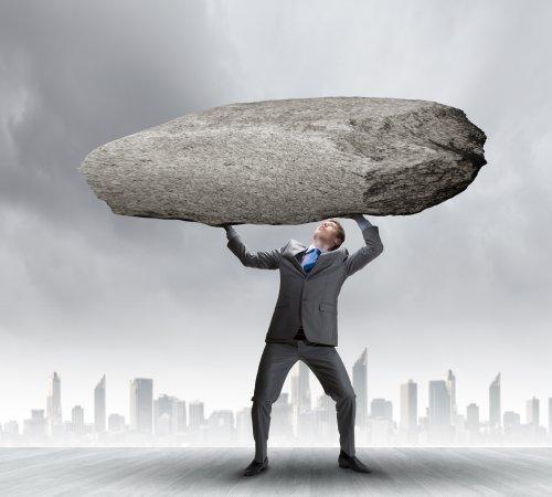 Ảnh chụp doanh nhân mạnh mẽ đang nắm giữ hòn đá lớn trên đầu