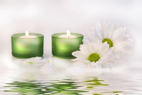 Hình ảnh hai ngọn nến màu xanh và hoa cúc phản chiếu trên mặt nước