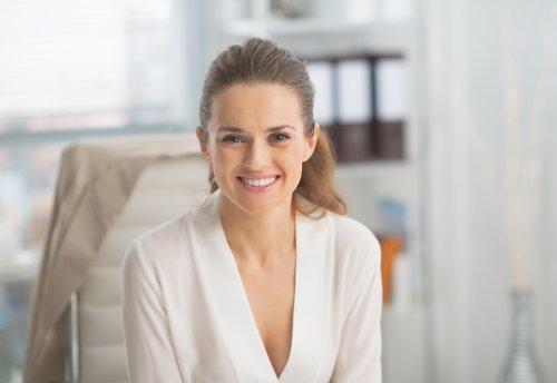Ảnh chân dung của người phụ nữ kinh doanh đang mỉm cười trong văn phòng