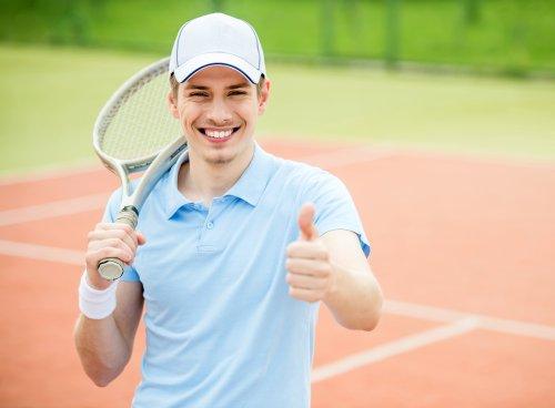 Ảnh chụp Người đàn ông trẻ chơi quần vợt tại sân vào buổi sáng.