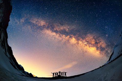Hình ảnh nhóm người đứng cùng nhau cầm tay chống lại Dải Ngân hà ở vùng núi.