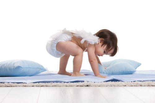 Hình ảnh Bé gái đeo đôi cánh thiên thần trắng, chơi với những chiếc gối màu xanh trên nền trắng