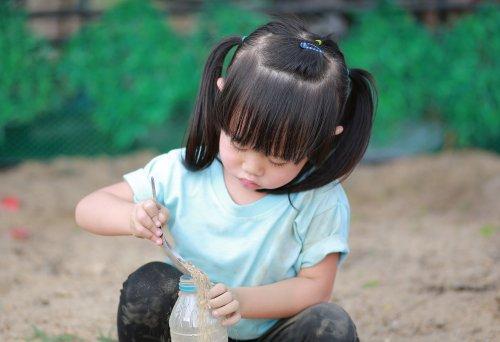 Ảnh Cô bé dễ thương đang chơi trong vườn với đất