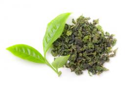 Ảnh chụp trà khô với lá trà xanh tươi tách biệt trên nền trắng