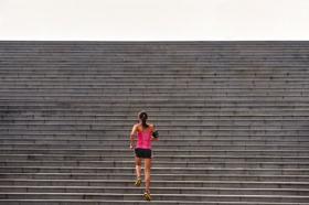 Hình ảnh người phụ nữ tập thể thao chạy lên cầu thang ngoài trời
