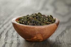 Ảnh trà xanh ô long trong bát gỗ, trên bàn gỗ sồi