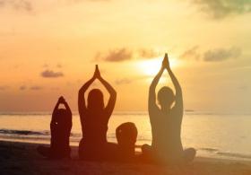 Hình ảnh gia đình tập yoga trên biển lúc hoàng hôn