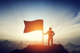 Ảnh chụp Người đàn ông tự hào đang treo cờ trên đỉnh núi