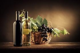 Ảnh chai rượu vang, trái nho và lá trong giỏ trên một chiếc bàn gỗ mộc mạc