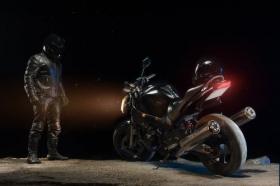 Ảnh người đàn ông trong trang phục da và đội mũ bảo hiểm đứng bên cạnh xe đạp vào ban đêm.
